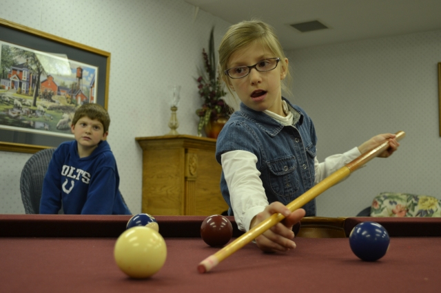 Two of the great-grandkids, Cameron and Abby, try to figure out how to play pool.