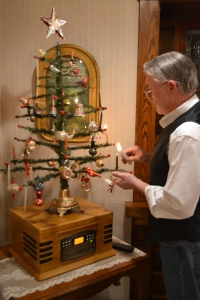 "Rick lights antique candle ornaments on a tree he made to resemble an old-fashioned ""feather tree."""