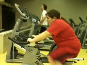 Colleen pedals on the spin bike at the Wells County YMCA.
