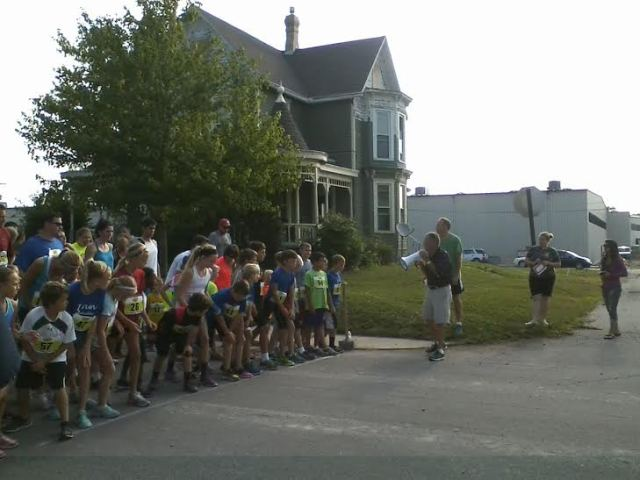 Dad prepares to start the kids' 1-mile race during the 41st Swiss Days Race on Saturday in Berne, Ind.