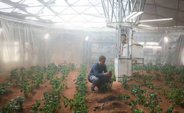"""In a scene from the movie """"The Martian,"""" Mark Watney works in an improvised greenhouse to grow potatoes in soil mixed with human waste."""